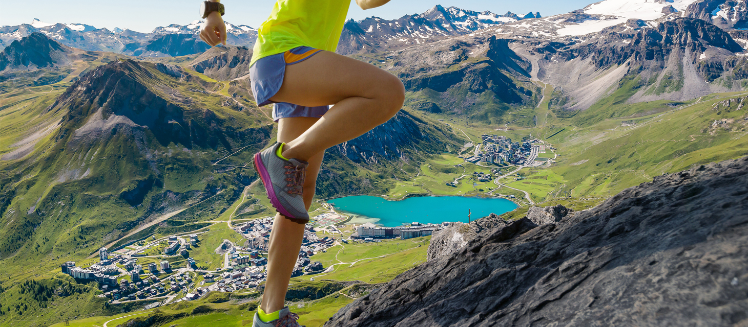 Young fitness woman trail runner running at mountain top